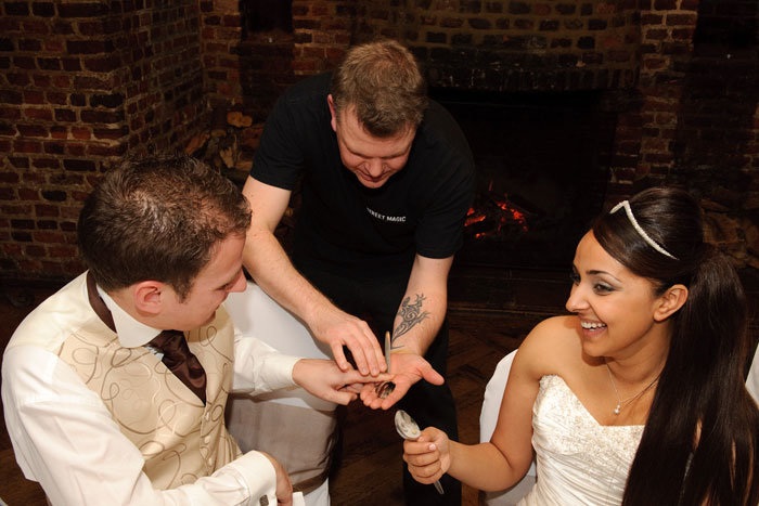 Wedding Magician preforms close up magic in the evening to bride and groom